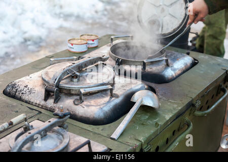 Cooking on a military field kitchen in field conditions - Stock Photo