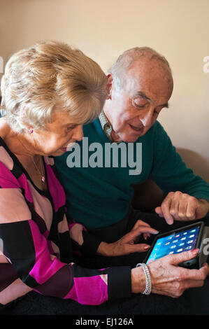 Vertical portrait of an elderly couple using an ipad together. - Stock Photo