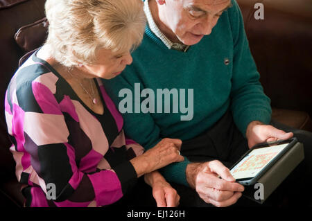 Horizontal portrait of an elderly couple using an ipad together. - Stock Photo