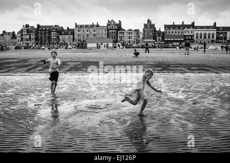 Children play on the shores of Weymouth Beach, in Dorset - Stock Photo