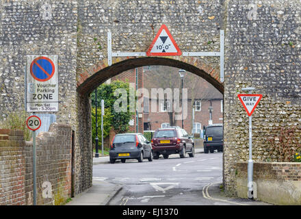 Height restriction on a narrow road, under an old stone wall. - Stock Photo