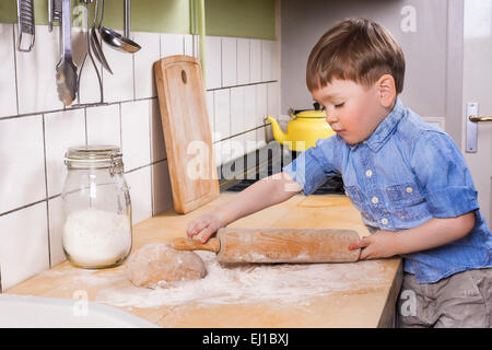 Cute toddler standing in the kitchen with a rolling pin and dough. - Stock Photo