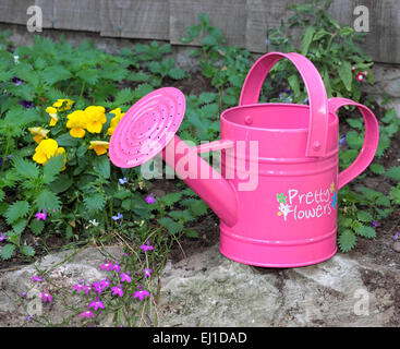 Child's pink watering can with the words Pretty Flowers written on the side - Stock Photo