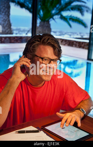 Happy mature man using his iPhone 6 smartphone and iPad air tablet computer in luxury vacation villa hotel interior - Stock Photo