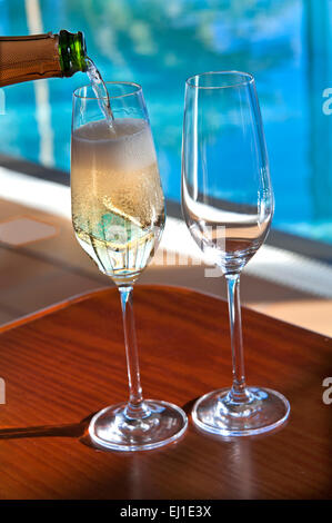 SPARKLING WINE POURING Close view on pouring chilled glasses of sparkling champagne wine on sunlit terrace with - Stock Photo
