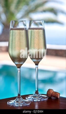 CHAMPAGNE Two freshly poured glasses of champagne and cork on alfresco terrace table with luxury infinity pool and - Stock Photo