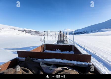 Travelling in the sledge of a snowmobile at Kebnekaise mountain area, Nikkaluokta, Kiruna, Sweden, Europe, EU - Stock Photo