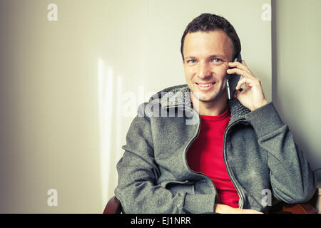 Portrait of sitting young Caucasian man talking on mobile phone. Vintage toned photo with old style filter effect - Stock Photo