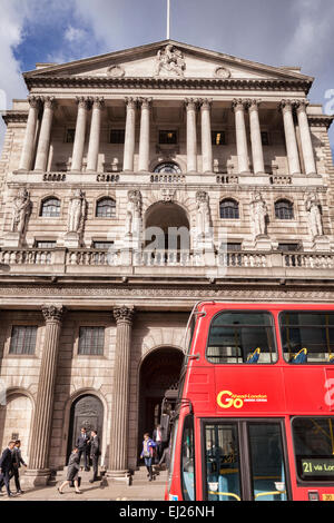 Red double-decker bus passing the Bank of England, Threadneedle Street, London. - Stock Photo