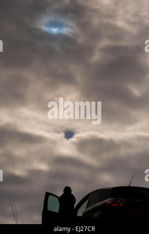 Ilkley Moor, West Yorkshire, UK. 20th March 2015. Silhouetted person stands watching the partial solar eclipse at - Stock Photo