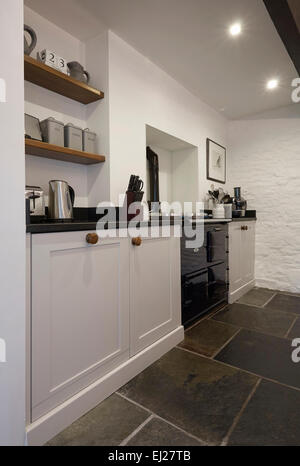 A White country style kitchen in a farmhouse in the UK with stone walls. - Stock Photo