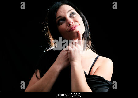Young woman with straight hair on dark background - Stock Photo