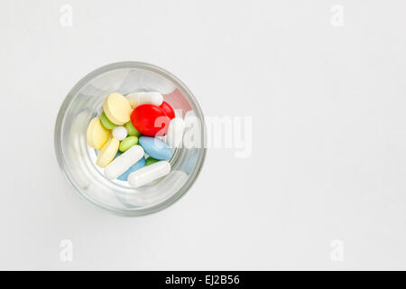 Many colorful pills and tablets in glass. Space for text - Stock Photo