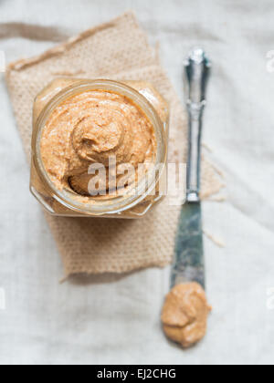 Vertical photo of homemade natural almond butter in a glass jar placed on rustic beige table cloth. View from above. - Stock Photo