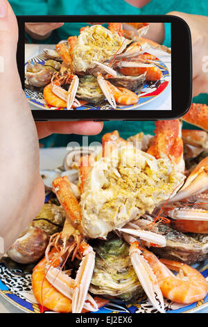 photographing food concept - tourist takes picture of plate with cut crab, oysters, shrimps and other seafood on - Stock Photo