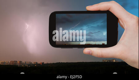 travel concept - tourist takes picture of lightning bolt in storm clouds over city in summer evening on smartphone, - Stock Photo