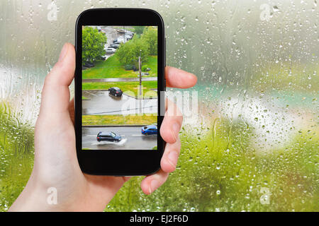 travel concept - tourist takes picture of shower in city from home window on smartphone, - Stock Photo
