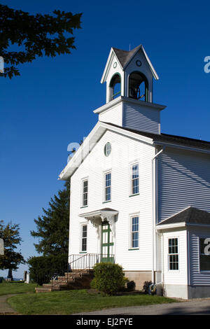The entrance of an old white country church with a bell tower sits on a hill with a blue sky background. - Stock Photo