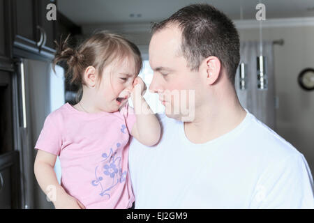 Angry upset girl with father inside the house - Stock Photo