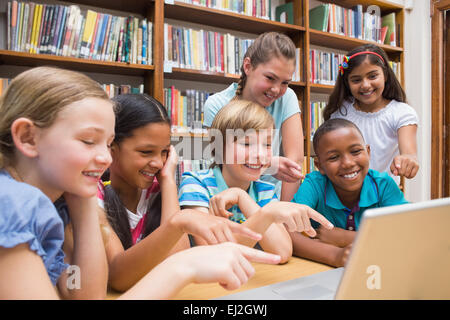 Cute pupils using tablet computer in library - Stock Photo