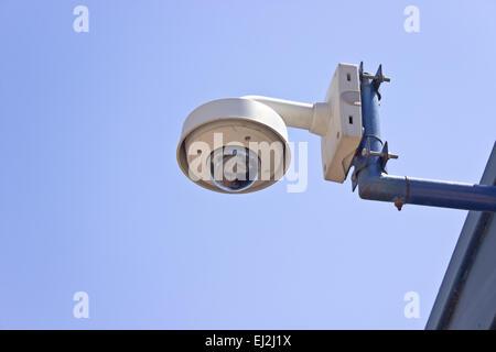 Hi-tech dome type surveillance camera over blue sky - Stock Photo