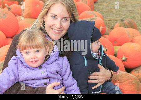 attractive Mother with kids Portrait in Pumpkin - Stock Photo