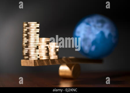 A seesaw with stacks of coins on the one side and on the other side the earth. - Stock Photo