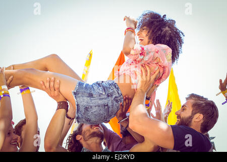 Happy hipster woman crowd surfing - Stock Photo