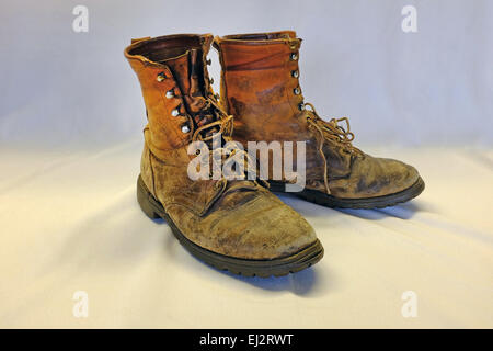 A pair of very old, very worn, hiking or work boots. - Stock Photo