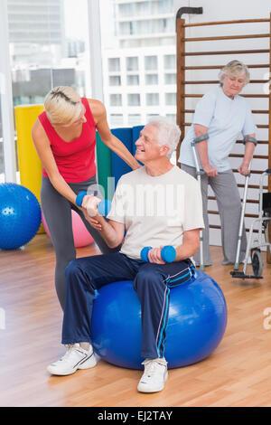 Trainer assisting senior man in lifting dumbbells - Stock Photo