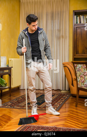 Young Handsome Man in Casual Outfit Holding Stick of a Broom, Looking Down Tired, at Home - Stock Photo