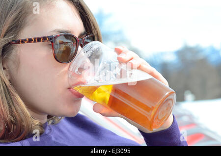 Young woman outdoors drinking a beer in sunglasses - Stock Photo