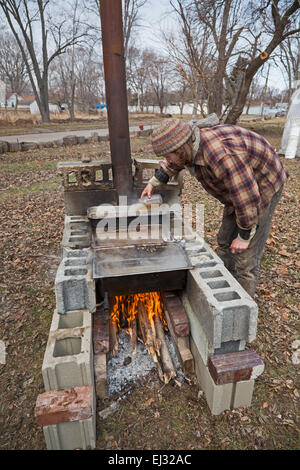 Detroit, Michigan - Kieran Neal boils sap from sugar maple trees over a wood fire to make maple syrup. - Stock Photo
