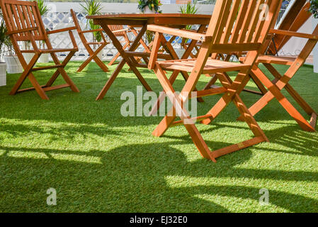 wooden chairs and table on the green grass - Stock Photo