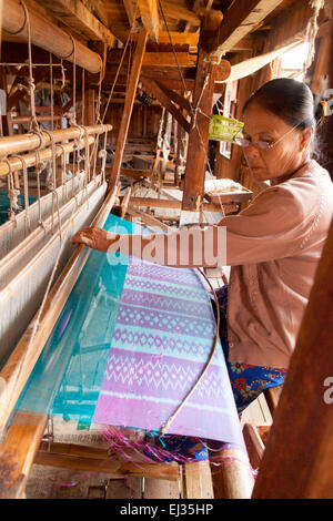 A burmese woman weaving lotus silk thread on a loom,  In Paw Khone village, Inle Lake, Myanmar ( Burma ), Asia - Stock Photo