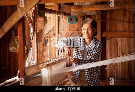 Elderly burmese woman weaving lotus silk at her loom, In Paw Khone village, Inle lake, Myanmar ( Burma ), Asia - Stock Photo
