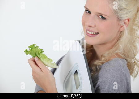 portrait of angel-faced blonde carrying scales with salad leaf in hand - Stock Photo