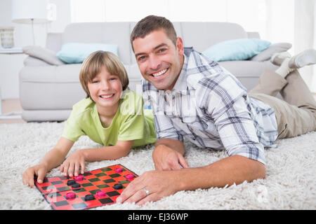 Father and son playing checker game on fur - Stock Photo