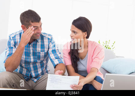 Stressed couple discussing over home finances - Stock Photo
