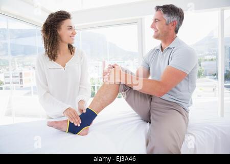 Doctor examining her patient foot - Stock Photo
