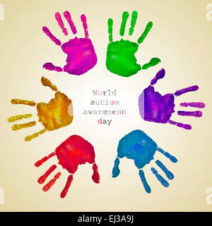 some handprints of different colors forming a circle on a beige background and the text world autism awareness day - Stock Photo