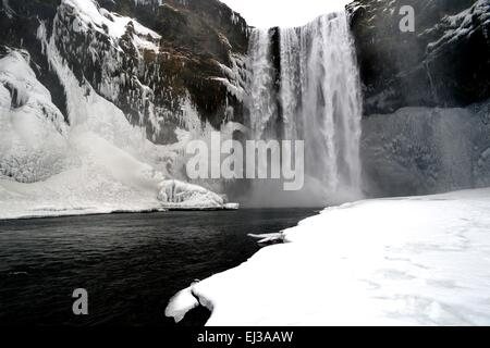 Skogafoss waterfall Iceland in snow during winter - Stock Photo