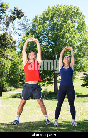Fit couple stretching in the park - Stock Photo