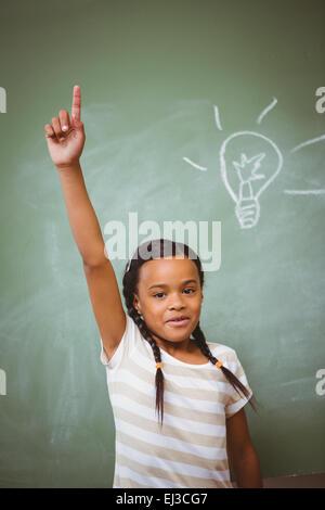 Little girl raising hand in classroom - Stock Photo
