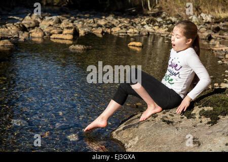 Nine year old girl gingerly testing the temperature of the Snoqualmie River, with her bare toes, near North Bend, - Stock Photo