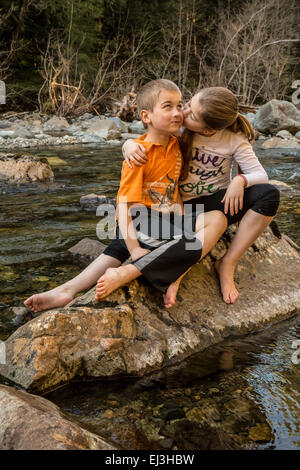 Nine year old girl giving her seven year old brother a hug and a kiss while sitting on a boulder in a shallow river - Stock Photo