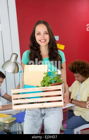 Casual businesswoman carrying her belongings in box - Stock Photo