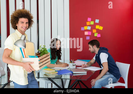 Casual businessman carrying his belongings in box - Stock Photo