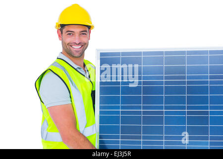 Smiling handyman in protective clothing carrying solar panel - Stock Photo