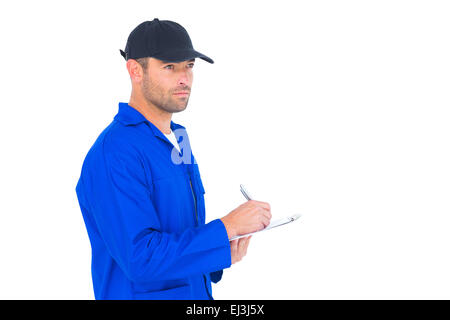 Mechanic in blue overalls writing on clipboard - Stock Photo